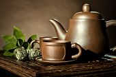 picture of loam  - horizontal photo still life of the clay teapot and cup on brown background - JPG