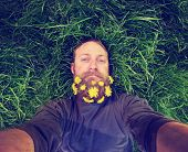 stock photo of tall grass  - a  hipster lying in tall grass with lilacs in his epic beard taking a selfie toned with a retro vintage instagram filter and light leaks  - JPG