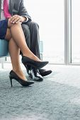 pic of office romance  - Low section of businessman flirting with female colleague in office - JPG