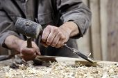 image of chisel  - Hands Of Carpenter With A Hammer And Chisel On The Workbench In Carpentry - JPG