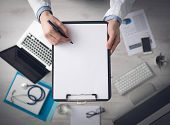 pic of medical equipment  - Doctor writing medical records on a blank sheet and holding a clipboard medical equipment and desktop on background top view - JPG