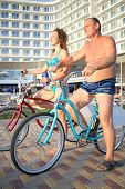 stock photo of bathing  - A man and a young woman in bathing suits on bikes on the hotel in the evening - JPG