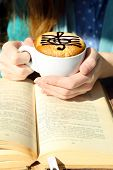 foto of treble clef  - Hands holding cup of cappuccino with treble clef on foam - JPG