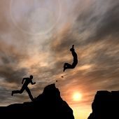 stock photo of gap  - Concept or conceptual young 3D man or businessman silhouette jump happy from cliff over  gap sunset or sunrise sky background - JPG