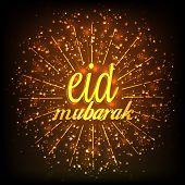 stock photo of eid mubarak  - Shiny golden text Eid Mubarak on fireworks brown background for muslim community festival celebration - JPG