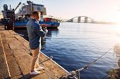 stock photo of street-rod  - Man casting with light rod on the river near the dock - JPG