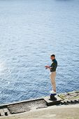 pic of street-rod  - Man casting with light rod on the river from the peir - JPG