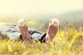 stock photo of toe  - Child with daisy between toes lying in meadow relaxing in summer sunshine - JPG