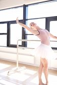 picture of ballet barre  - Young Graceful Ballerina Warming Up and Doing Barre Exercises in Studio - JPG