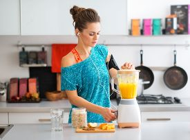 image of oats  - A sporty woman is standing in her kitchen making a smoothie with fresh seasonal fruits nuts and oats to complete her healthy start to the morning. ** Note: Shallow depth of field - JPG