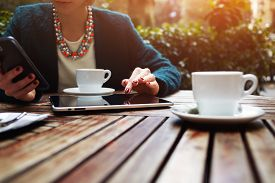 picture of wooden table  - Cup of coffee on the foreground with elegant young woman using busy touch screen tablet at the coffee shop wooden table work break of business people flare sun light - JPG