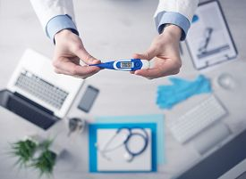 stock photo of temperature  - Doctor measuring temperature and holding a digital thermometer desktop with medical equipment and computer on background top view - JPG