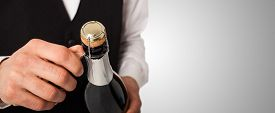 picture of celebrate  - Portrait of a waiter holding a champagne bottle - JPG