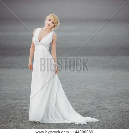 Bride outdoors in a desert. Beautiful woman posing in white wedding dress. Gray background with copy space. Some fine art noise. Square picture format.