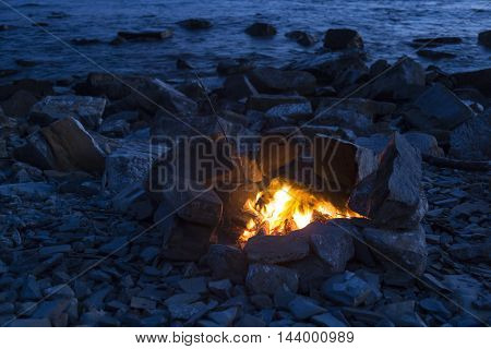 Fire by the sea during sunset. Amazing place for relaxing and harmony.