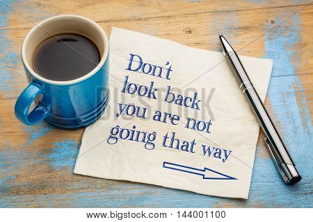 Do not look back  you are not going that way - handwriting on a napkin with a cup of espresso coffee