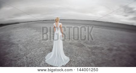 Bride outdoors in a desert looking afar. Beautiful woman in white dress full body length. Stretched wide landscape fish eye lens photo. Gray background copy space good for texting. Some fine art noise.