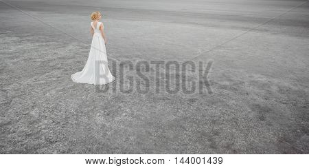 Bride outdoors in a desert looking afar. Beautiful woman in white dress full body length. Stretched wide landscape photo. Gray background copy space good for texting. Some fine art noise.