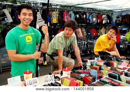 New York City - July 27 2007: Three Chinese youths selling wallets and leather goods at the annual Greenwich Avenue Street Festival in Greenwich Village