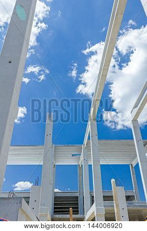 Perspective view of concrete pillars edifice in progress of growing into tall building with cloudy sky in background.