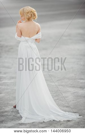 Bride outdoors in a desert looking afar in sensual pose, touching her lips. Beautiful woman in white dress full body length. Gray background.