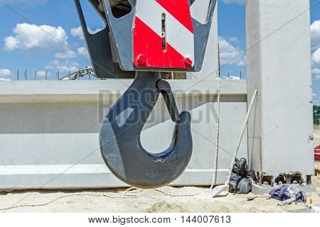 Big crane hook with red stripes is hanging building site in background.
