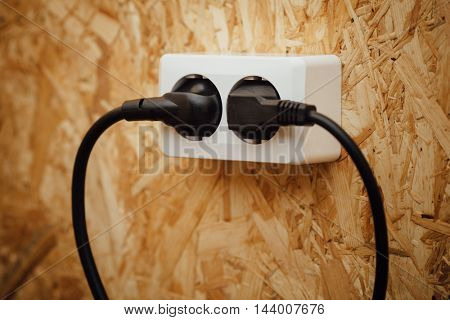 AC power plug and socket, wooden osb wall background