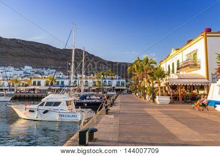PUERTO DE MOGAN, GRAN CANARIA, SPAIN - APRIL 25, 2016: Marina of Puerto de Mogan at sunset, a small fishing port on Gran Canaria, Spain. Puerto de Mogan is called a Little Venice of the Canaries.
