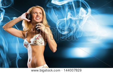 Attractive girl in white bikini and headphones on color background