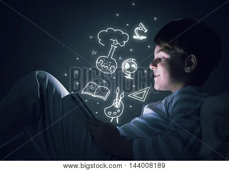 Teenage boy in pajamas lying in bed using tablet pc
