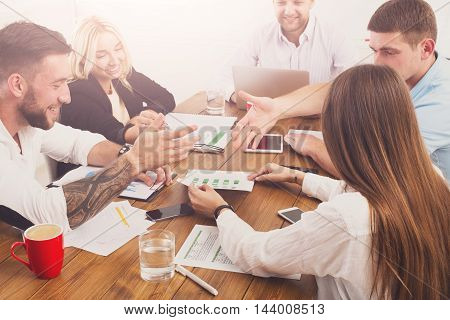 Business meeting. Young happy businessmen and women at modern office, team corporate discussion at workplace. Brainstorming and communication with partners for startup, planning development strategy