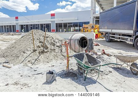 Cement mixer machine is at construction site with two wheelbarrows tools sand and cement bag.
