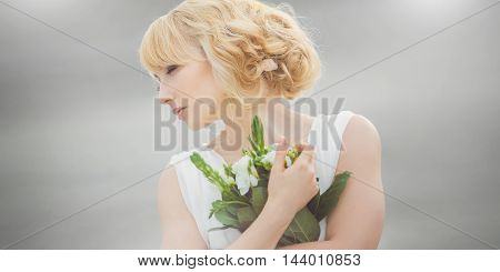Portrait of a young beautiful bride with closed eyes gently embraces wedding bouquet outdoors on gray background. Professional make-up and hair-style. Stretched wide landscape photo.