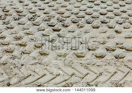 Pattern tracks of huge road roller with spikes in soil sand at construction site