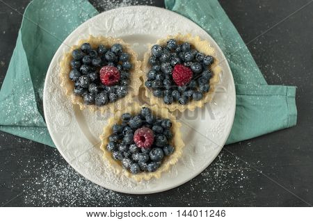 Sand basket with fresh blueberry and raspberries on white plate.