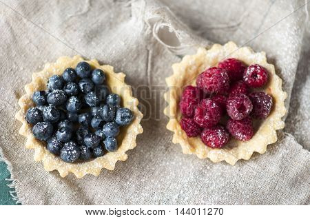 baked sand basket with fresh berries on tablecloth.