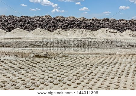 Soil layers on building site blue sky ground wavy piles of sand tracks of spikes from steamroller.