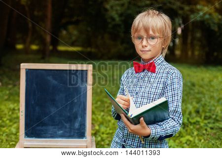 stylish blond little boy with glasses with a notebook. Back to school concept.