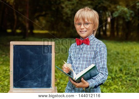 stylish blonde cheerful little boy in glasses. Back to school concept.