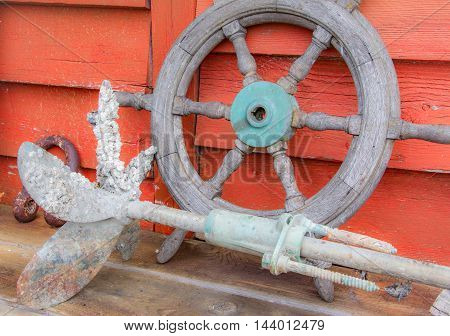 Nautical display of antique ship's wheel and boat prop covered in barnacles