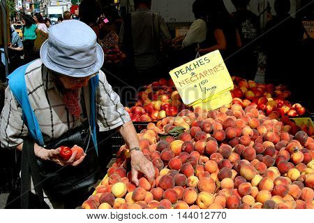 New York City - September 24 2005: Woman buying fresh peaches at the Union Square Farmer's Market