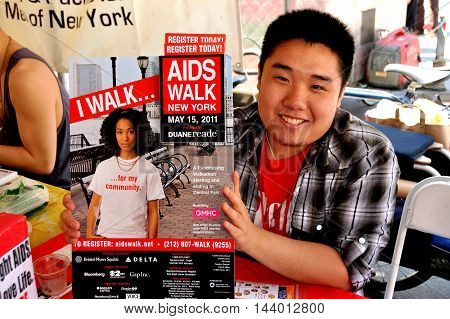 New York City - May 7 2011: Asian youth at the Asian and Pacific Islander Coalition on HIV/AIDS with an AIDS Walk poster at the 32nd Asian America & Pacific Islander Heritage Festival 2011 in Union Square