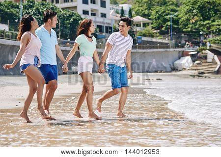 Joyful Vietnamese couples enjoying weekend on the beach