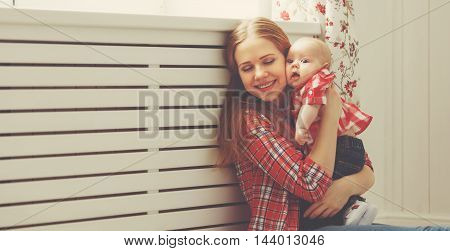 happy family mother and baby playing at home window