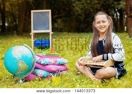 beautiful girl writes in a notebook and learn. Concept back to school