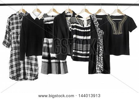 Set of black and white clothes on clothes racks isolated over white