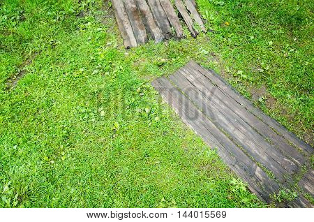 Old Gray Wooden Decking On Green Lawn Grass