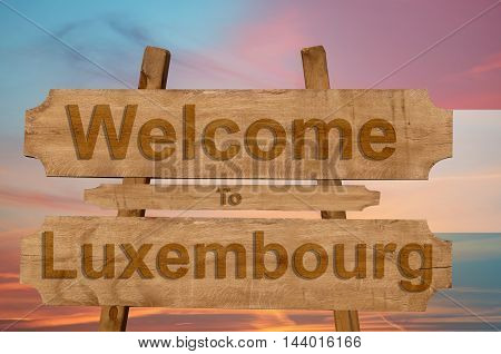 Welcome To Luxembourg Sign On Wood Background With Blending National Flag