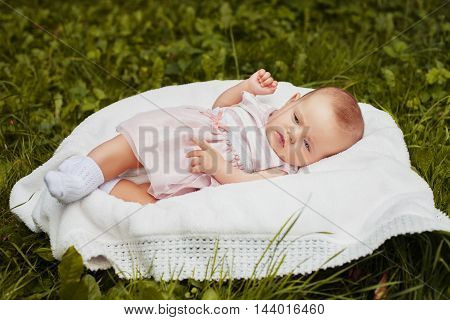little an infant in soft clothes lying in a basket