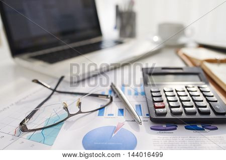 Business document, calculator and glasses on table of entrepreneur
